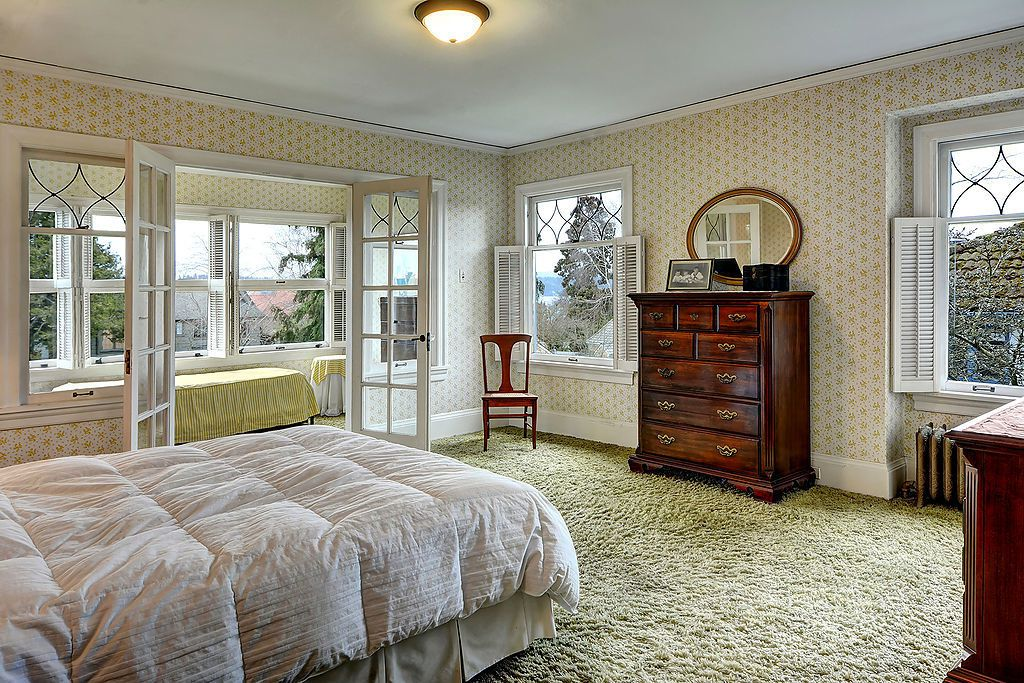 A bedroom with a bonus room behind it, separated by French doors