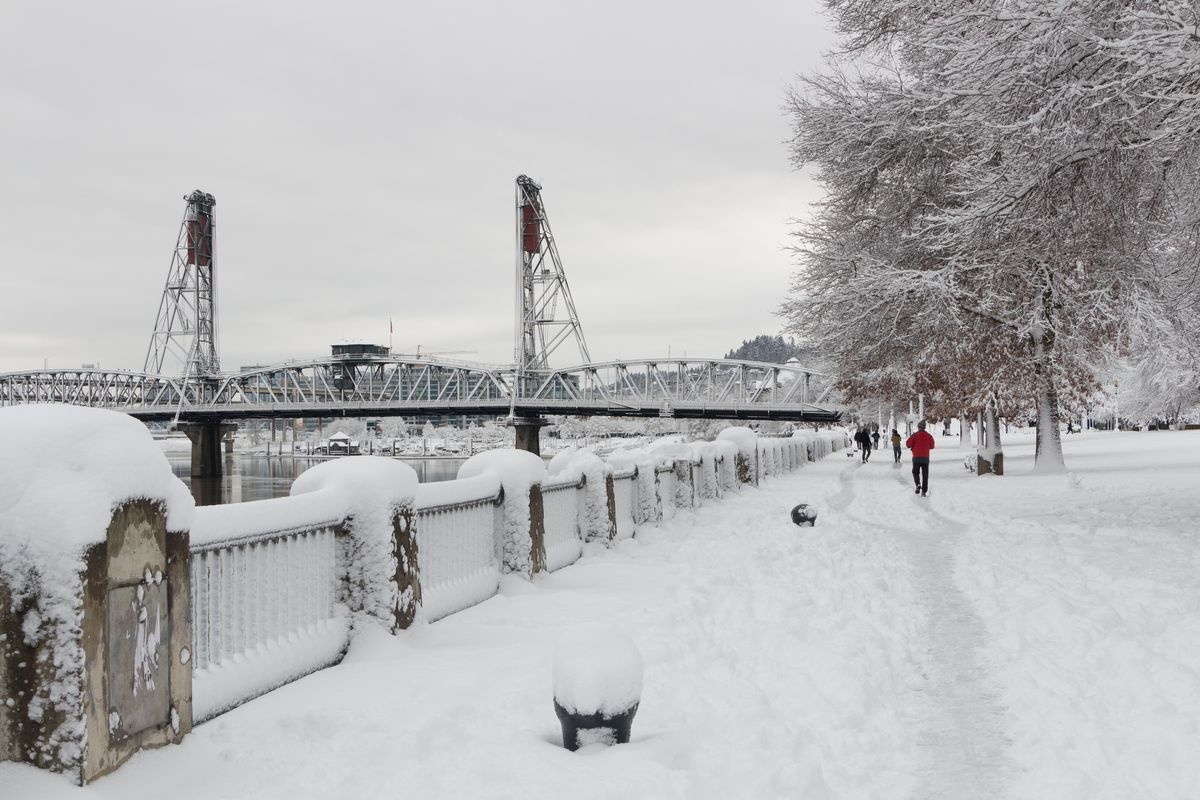 The Hawthorne Bridge is caked in snow crossing the Willamette River, as people walk along the waterfront