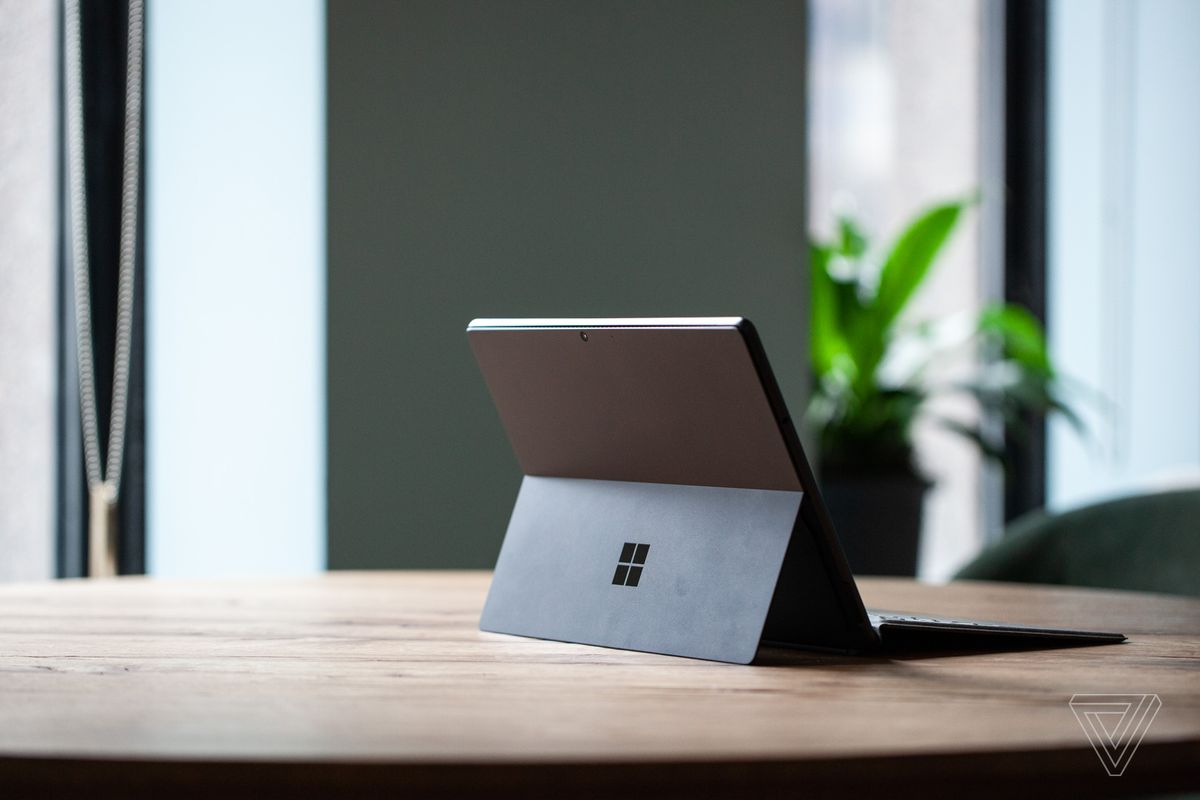 The Surface Pro 8 on a table seen from the back to the right, open, with the Signature Keyboard attached and the kickstand out. In the background is a green wall and a potted plant.