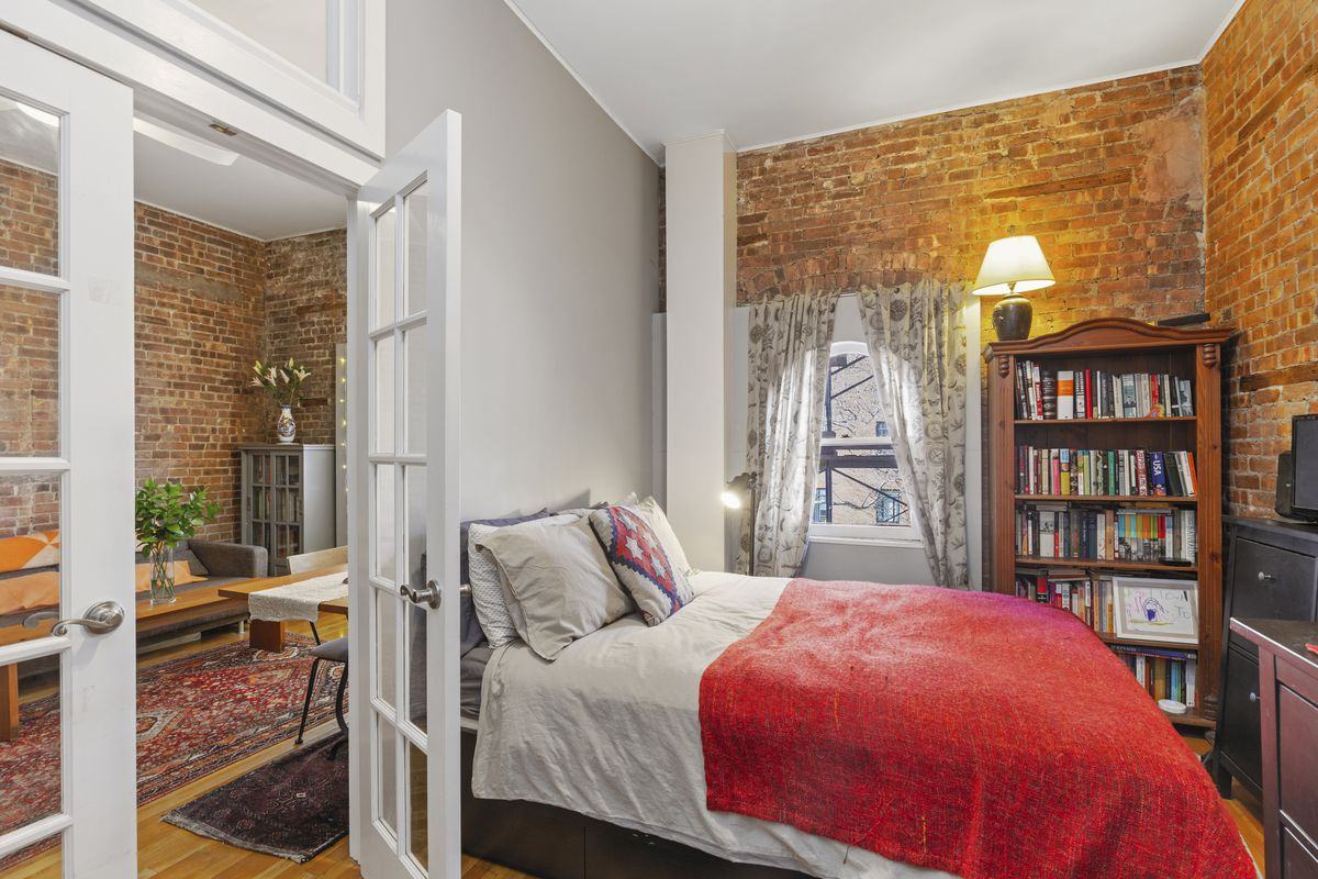 A bedroom with a medium-sized bed, exposed brick, and an arched window.