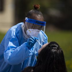 Phlebotomist Crystal Bovan, with Simple Laboratories, collects a nasopharyngeal swab sample to test for the coronavirus for a woman at the lab's drive-thru testing site in the parking lot of St. Rosalie Catholic Parish in Harwood Heights, Friday, May 1, 2020.