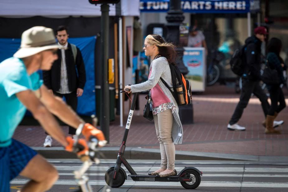A picture of a woman riding a bird scooter down a city street.