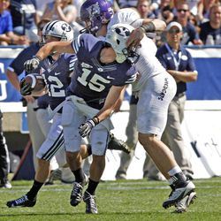 Brigham Young Cougars Alex Kuresa (15) has head head twisted as he blocks for Brigham Young Cougars wide receiver JD Falslev (12) as Brigham Young University defeats Weber State University in football 45-6 Saturday, Sept. 8, 2012, in Provo, Utah.