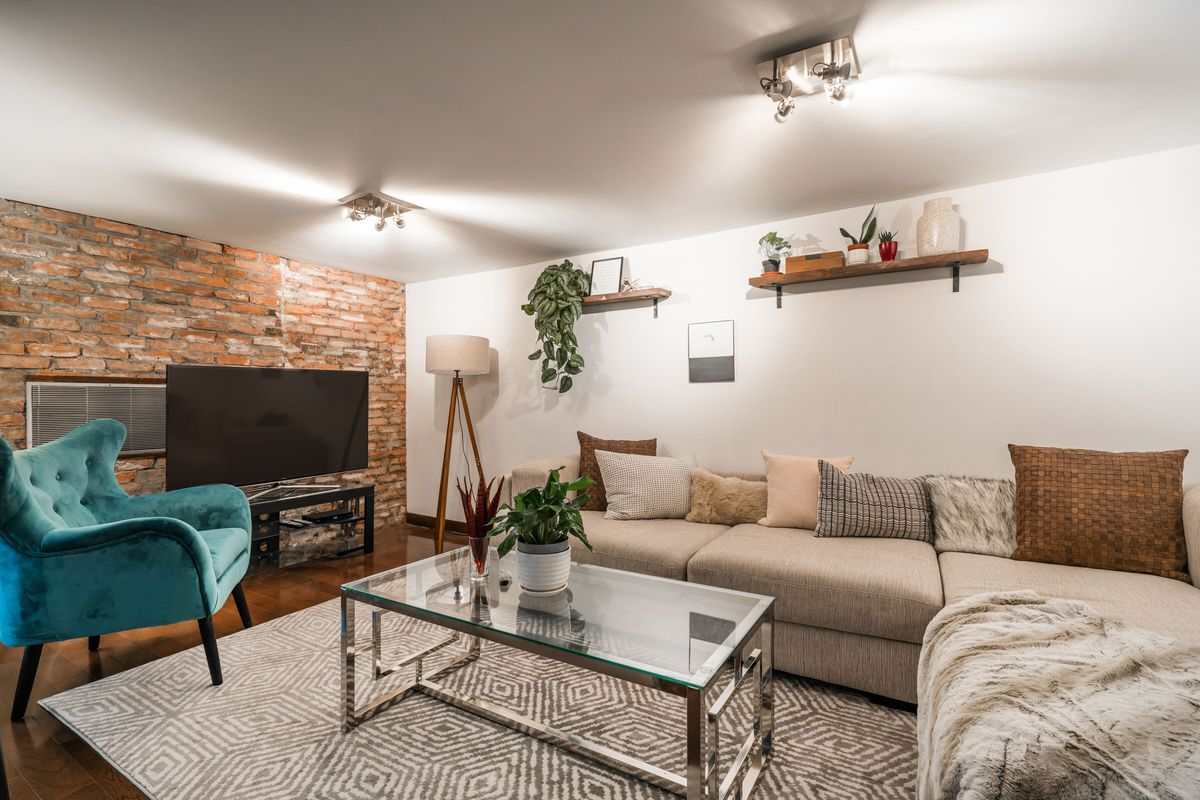 A living area with a beige couch, exposed brick, white walls, and hardwood floors.