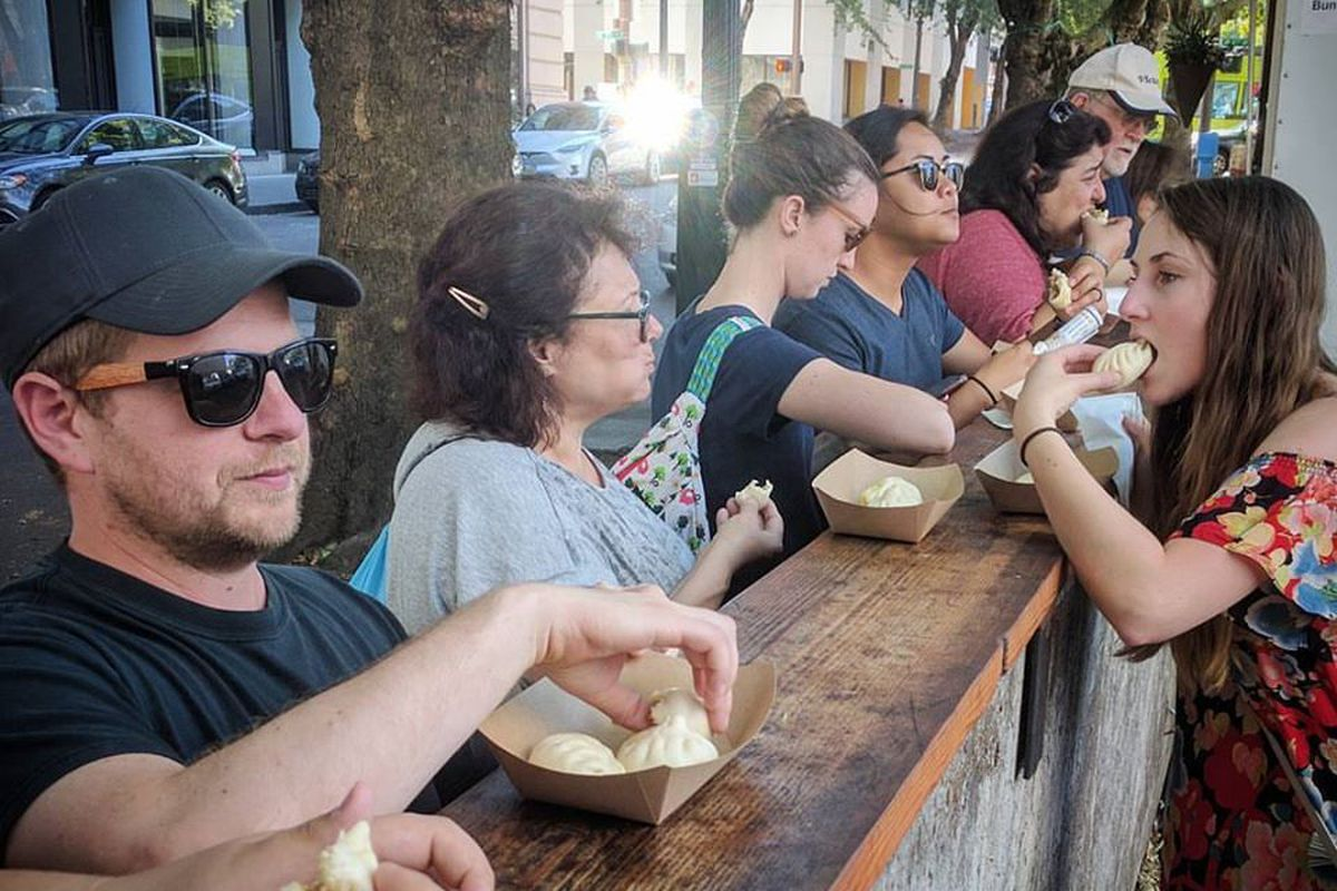 A line of customers eat bao over a wooden railing at the original cart