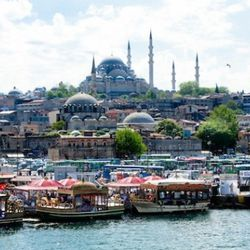 A partial view of Istanbul as seen from the Galata bridge that spans the Golden Horn. It is common to see families and old men fishing off the bridge during the day. The Suleymaniye Mosque looms high in the background. At the base of the bridge there are