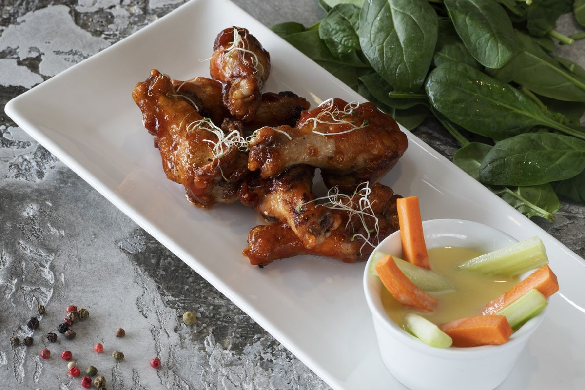 A plate of Buffalo wings seen at Rooster Grill bar and...
