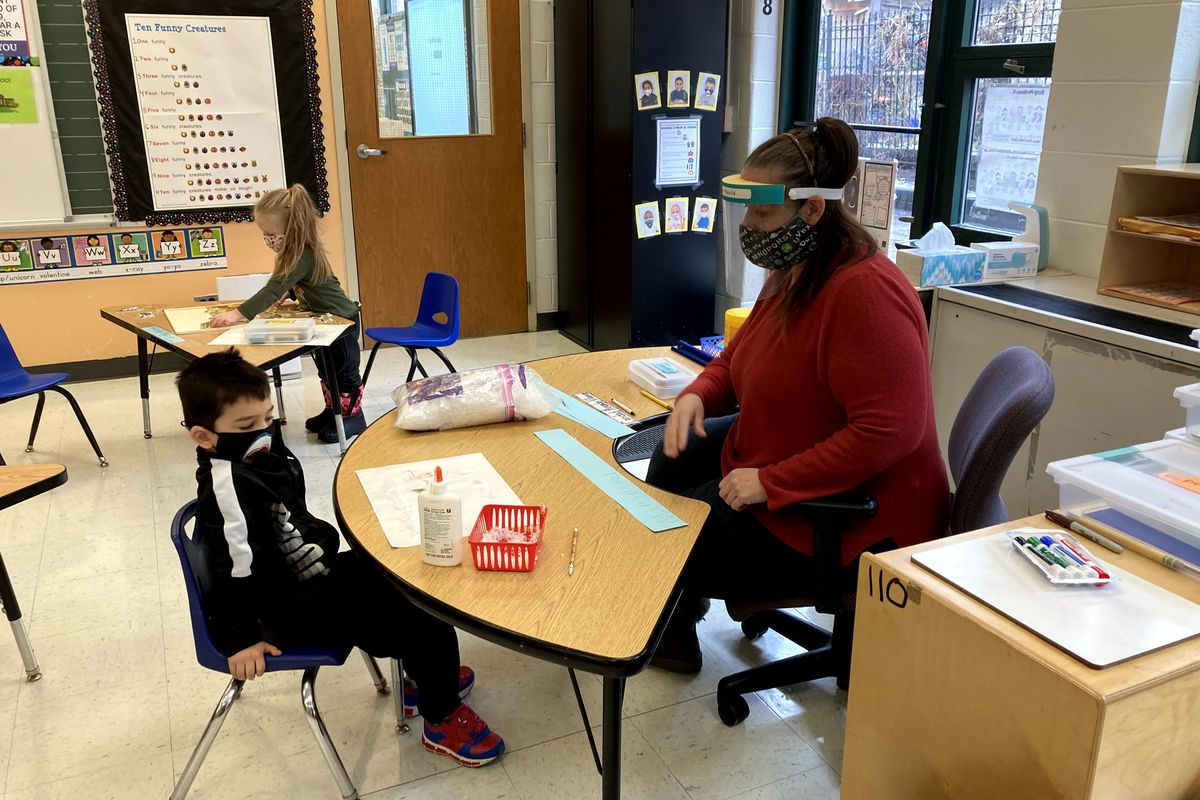 Masked teacher and masked student face each other across a semicircular desk in a classroom.