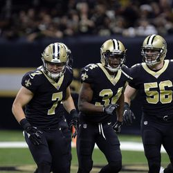 New Orleans Saints special teams player Taysom Hill, left, celebrates with Justin Hardee (34) and Michael Mauti (56) after stuffing a return against the Atlanta Falcons in New Orleans, Sunday, Dec. 24, 2017.