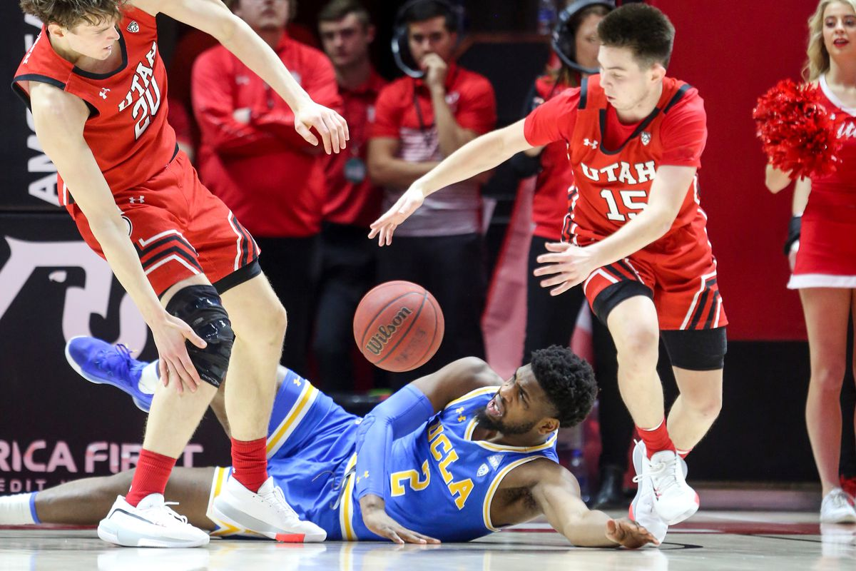 UCLA Bruins forward Cody Riley (2) attempts to get up while Utah Utes forward Mikael Jantunen (20) and guard Rylan Jones (15) go for the ball at the Jon M. Huntsman Center in Salt Lake City on Thursday, Feb. 20, 2020.