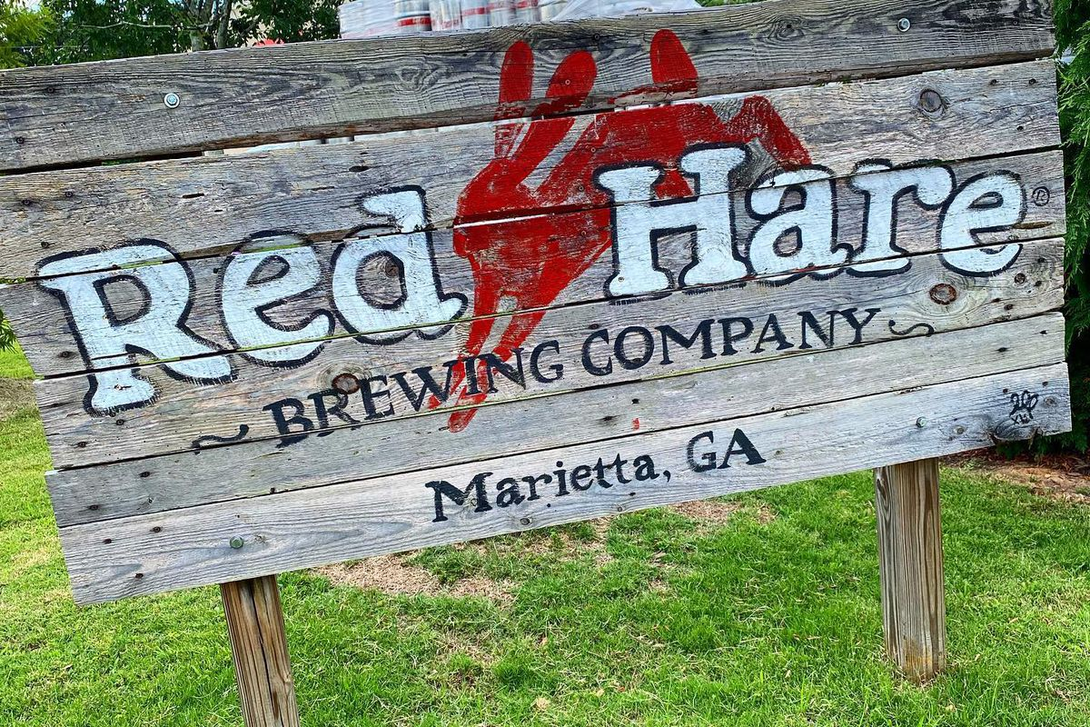 The weathered wooden sign on two posts in the ground for Red Hare Brewing outside it's Marietta Georgia brewery