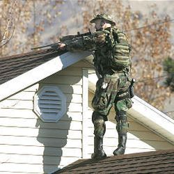 A SWAT member stands on the roof of a Springville home as the team surrounds a house where a man is holed up.