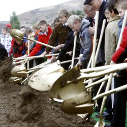 Elder Dallin H. Oaks along with 12 year old deacons from the Payson turn over the dirt as thousands turn out in the rain Saturday, Oct. 8, 2011 for the ground breaking for the Payson Temple.