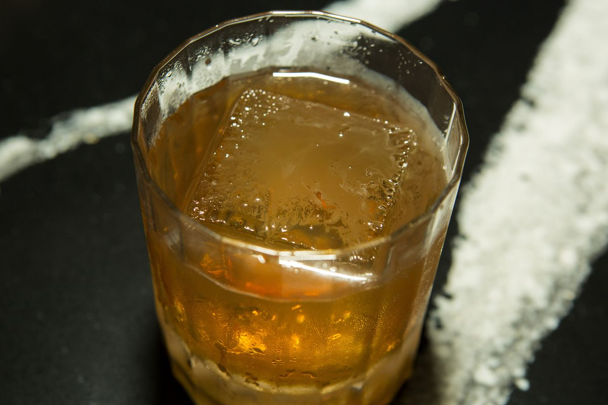 A drink in a glass with a large block of ice.