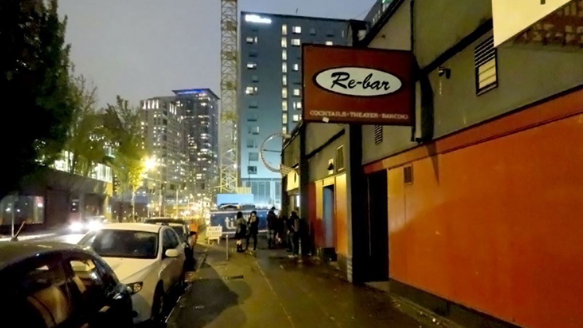 """A black, one-story building with a red stripe down the middle runs down the right side of the photo, which also shows a wide sidewalk and a line of parked cars to the left. A sign on the building says """"Re-bar."""""""
