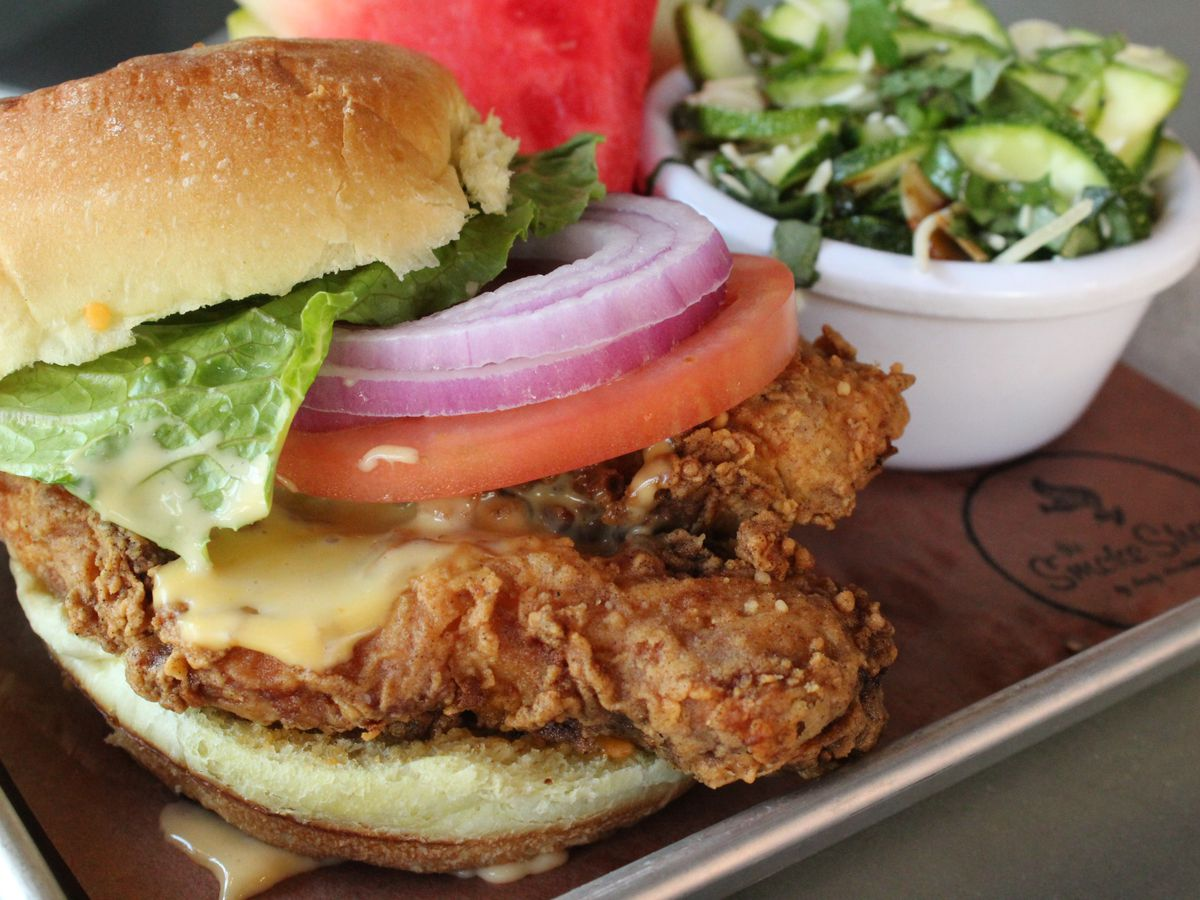Two crispy pieces of fried chicken sit on a bun, topped with cheese, lettuce, tomato, and onion. The bun is on brown paper on a metal tray; there's a Smoke Shop logo on the paper. A small white bowl of pickles and a watermelon slice are also on the tray.