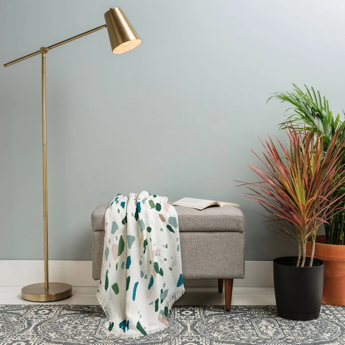 A terrazzo-patterned blanket atop an ottoman, flanked by a floor lamp and indoor plants.