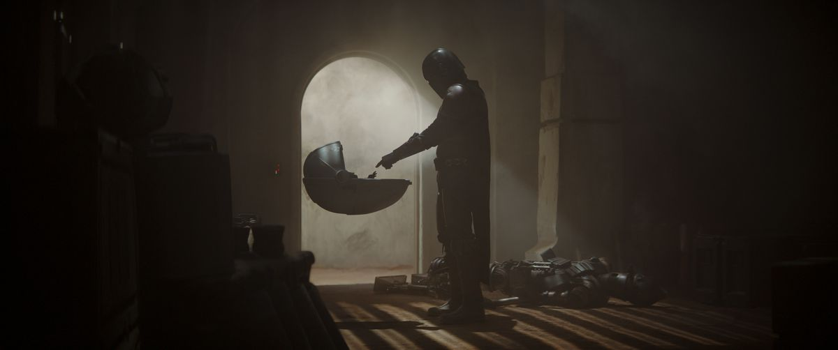 The Mandalorian and Baby Yoda touch hands, silhouetted by bright light from a door in the far wall. IG-11 lies dead on the ground.
