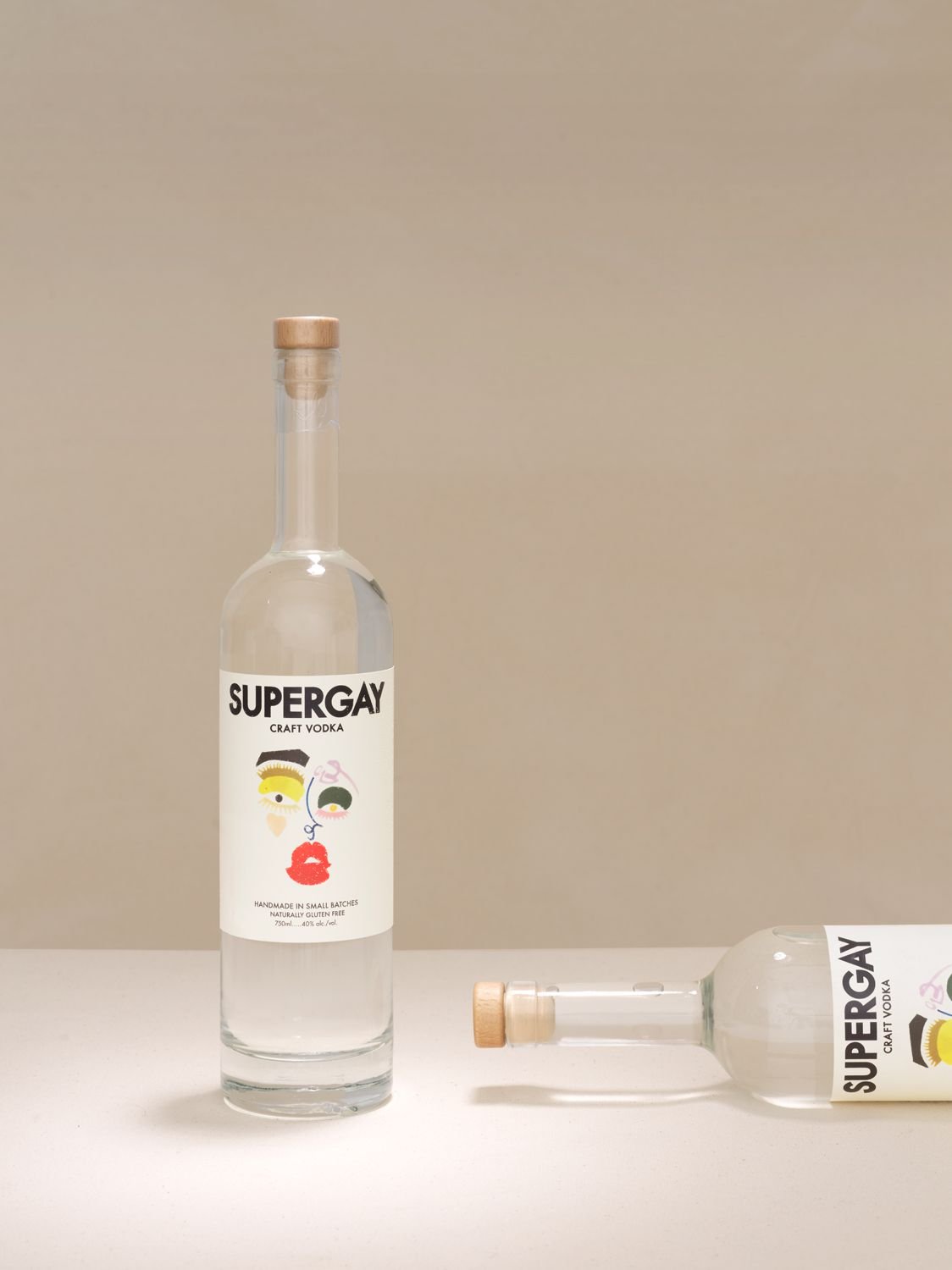 Two tall bottles with a clear liquid, one standing and one sitting flat on a table against a white background