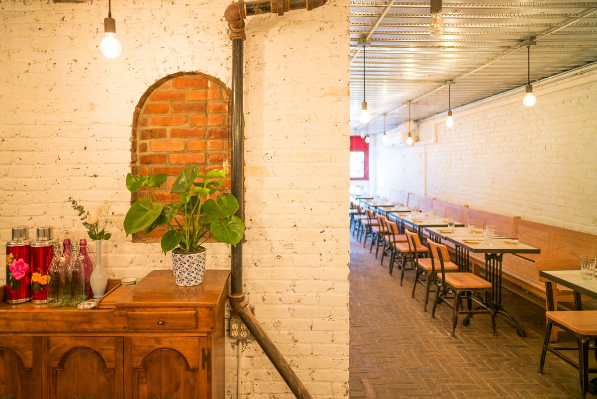 A restaurant dining room with whitewashed exposed brick walls and wooden tables