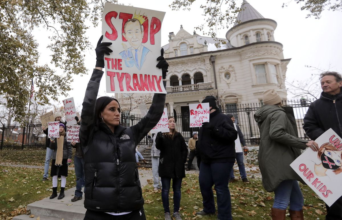 "Stephanie Grant holds a ""Stop the Tyranny"" sign during a protest of Gov. Gary Herbert's mask mandate and new COVID-19 restrictions outside of the Governor's Mansion in Salt Lake City on Monday, Nov. 9, 2020."