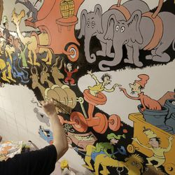 """In this May 4, 2017 photo John Simpson, left, project director of exhibitions for The Amazing World of Dr. Seuss Museum, paints a mural based on artwork in the Dr. Seuss book """"Did I Ever Tell You How Lucky You Are?"""" on a wall at the museum, in Springfield, Mass. The new museum devoted to Dr. Seuss, which opened on June 3 in his hometown, features interactive exhibits, a collection of personal belongings and explains how the childhood experiences of the man, whose real name is Theodor Geisel, shaped his work."""