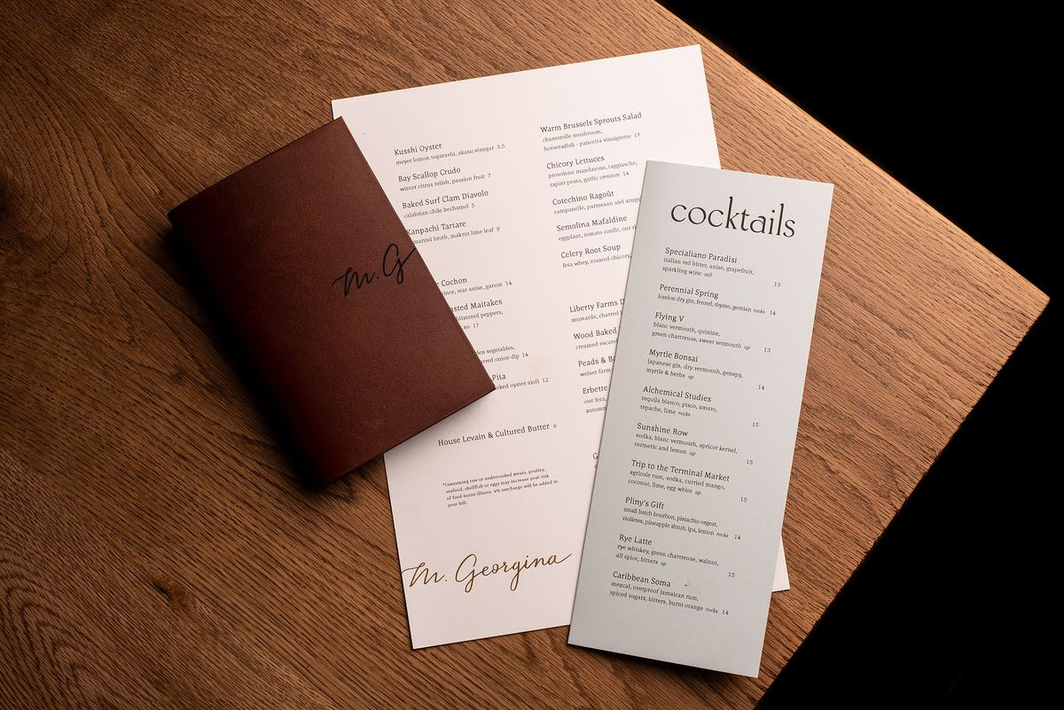 Menus and details for a new restaurant sit on a wooden table.
