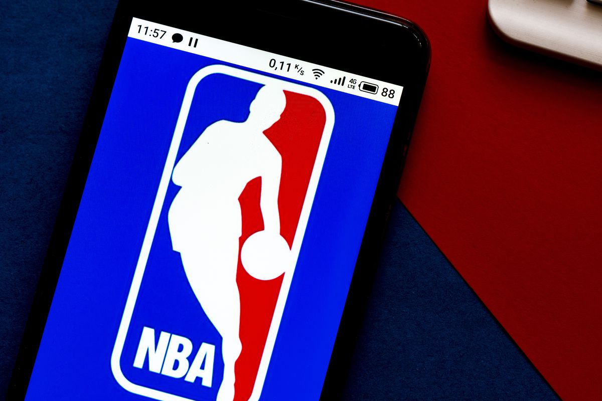 In this photo illustration an NBA logo seen displayed on a...