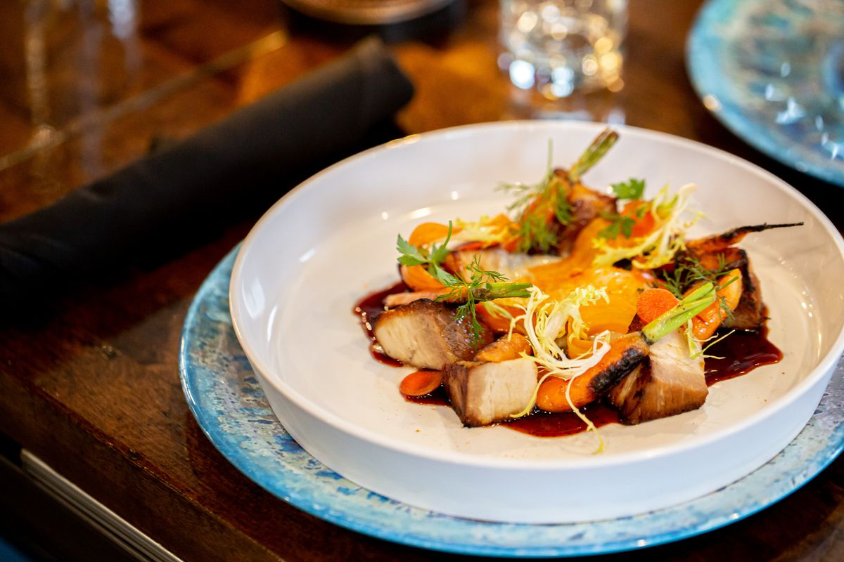 Slow-braised pork belly served with charred carrots and poached egg