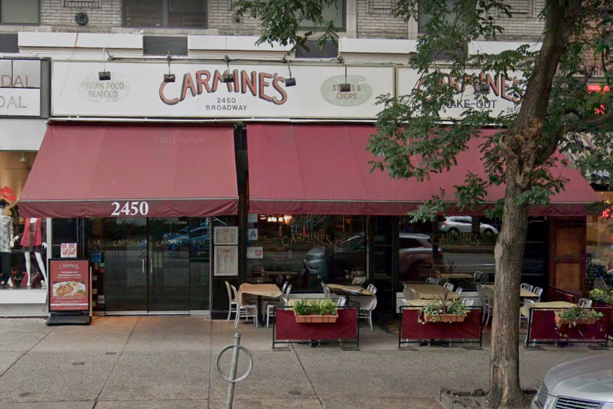 """The exterior of a restaurant with red awnings and a white sign above that reads """"Carmine's"""" in red lettering."""