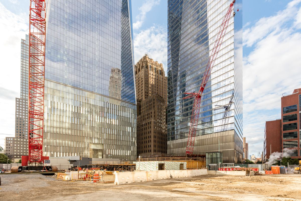 A construction site with two cranes. Two tall buildings with glass exteriors are behind the site.