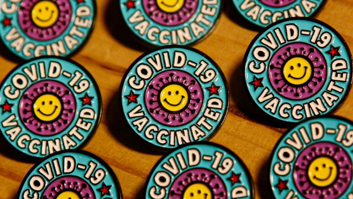 """插图画家内特·杜瓦尔(Nate Duval)的疫苗别针,上面有一个带有突刺蛋白的笑脸和""""COVID-19疫苗接种""""的字样。"""