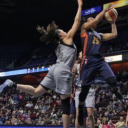Connecticut Sun's Alyssa Thomas (25) goes to the basket past San Antonio Stars' Dearica Hamby (5).