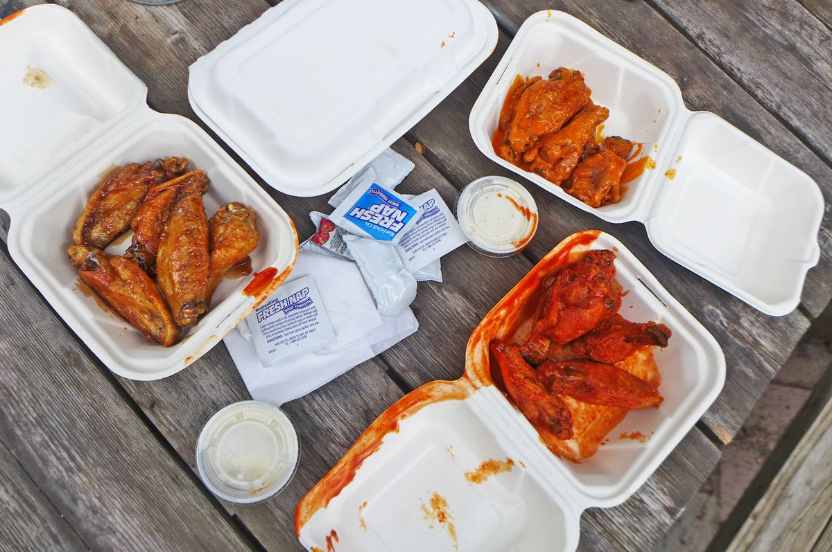 Three styrofoam tubs of chicken wings in various shades of red on a rustic picnic table.