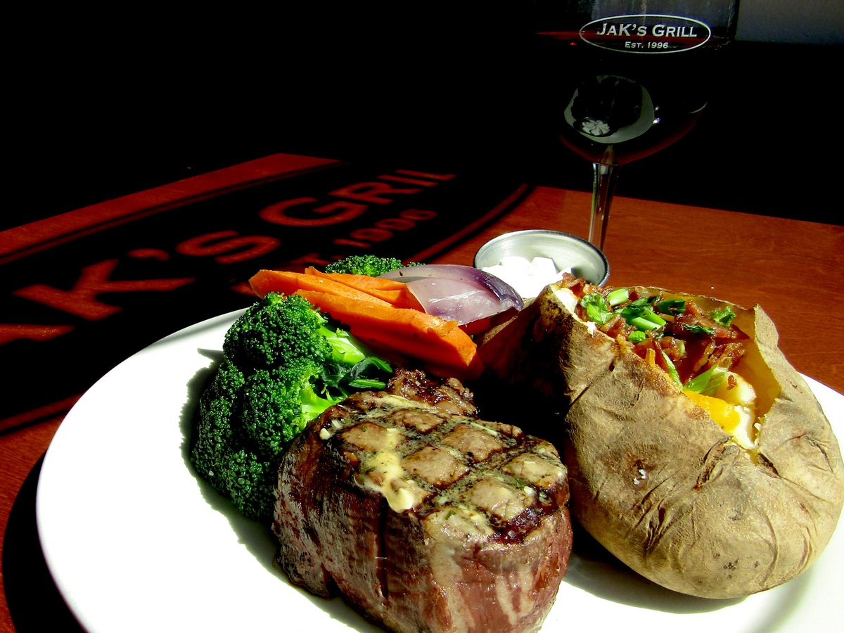 Steak, baked potato, a side of vegetables, and a glass of wine on a wood table.