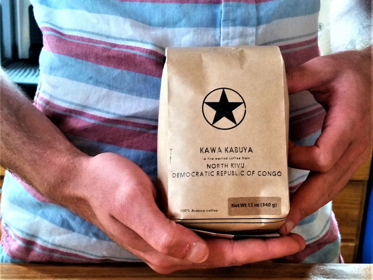 A person holds a bag of coffee beans labeled with Rising Star Coffee Roasters logo