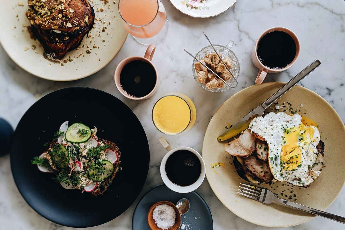 An overhead shot shows cups of coffee and mimosas scattered among plates of brunch items, including a ham and egg smorrebrod, a trout salad toast, and more