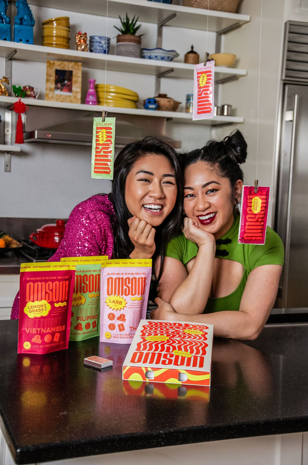 """Two people lean on a granite countertop with brightly colored packages dangling from the ceiling. On the counter, additional packages sit and are labeled """"Omsom"""""""