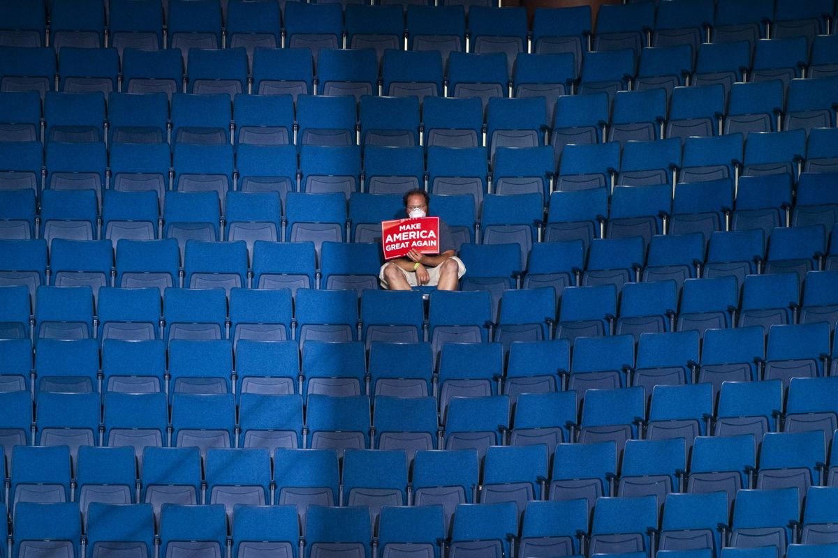 A lone Trump rally attendee sits alone with a bright red Trump sign, surrounded by empty blue stadium seats.