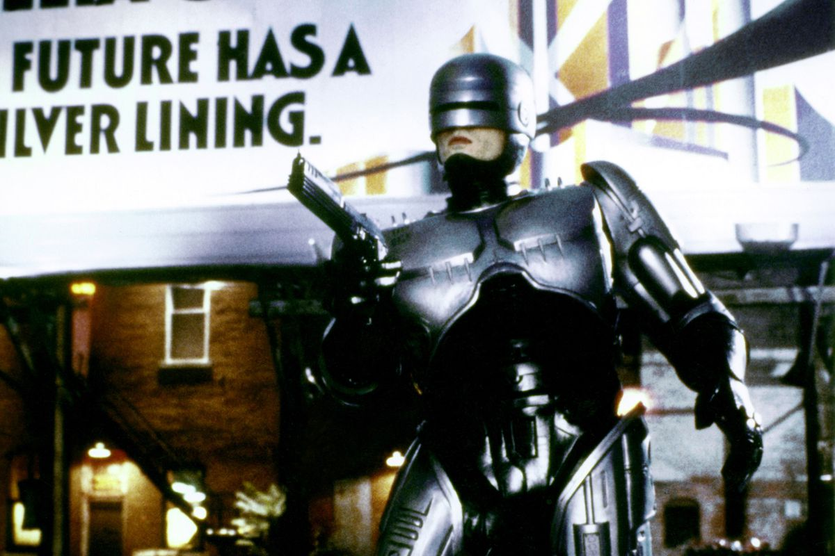 A photo of RoboCop standing with his gun drawn in front of a Delta City billboard from the 1987 movie RoboCop.
