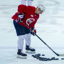 Dmitry Orlov smiles as he collects pucks at Capitals morning skate.