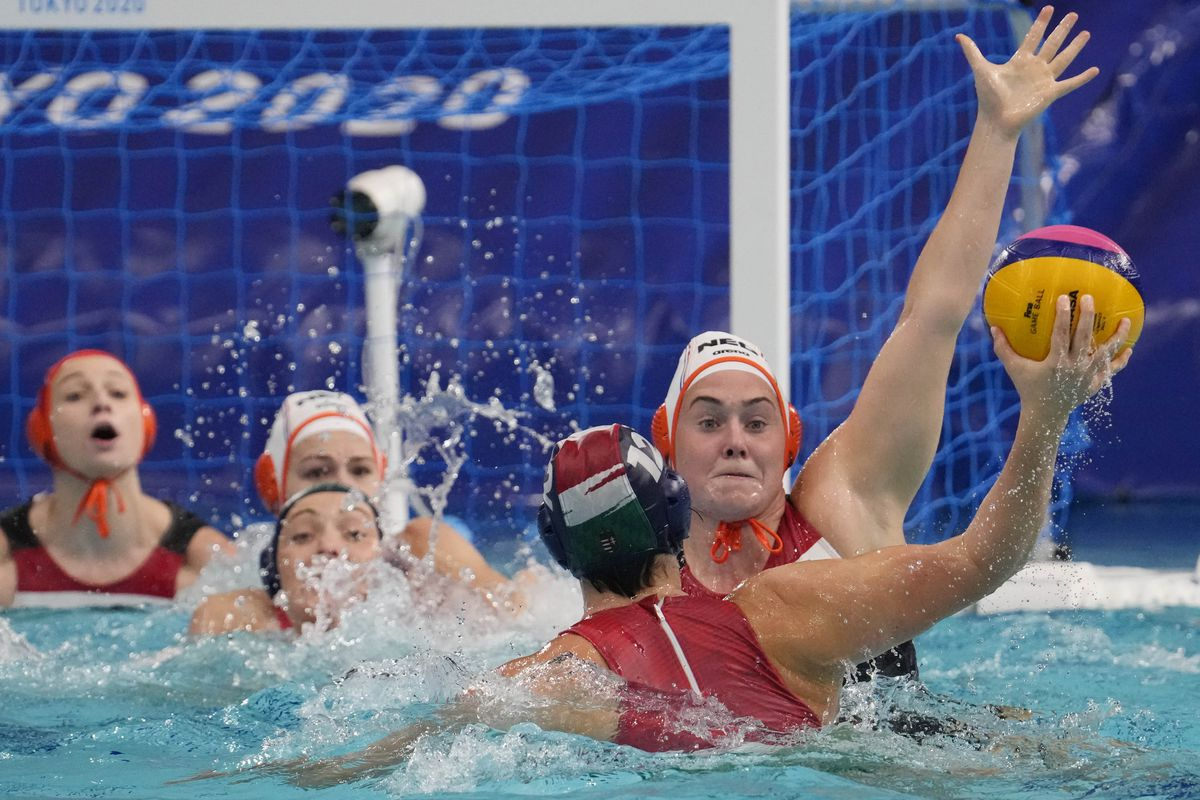 Team Netherlands centre forward Kitty Joustra (7) defends against Team Hungary driver Krisztina Garda (12) in a women's water polo quarter final match during the Tokyo 2020 Olympic Summer Games at Tatsumi Water Polo Centre.