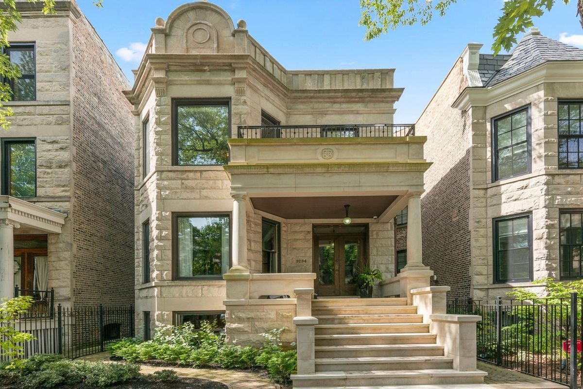 A two-story greystone with landscaping.