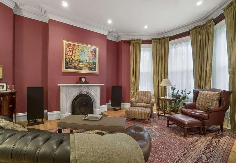 A spacious living room with a large bow widow and furniture as well as a fireplace.
