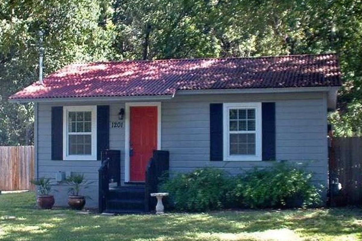 small gray frame bungalow with red door
