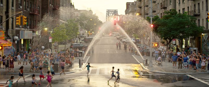 A busy street scene, with fire hydrants creating fountains for children to run through and the George Washington Bridge in the background.