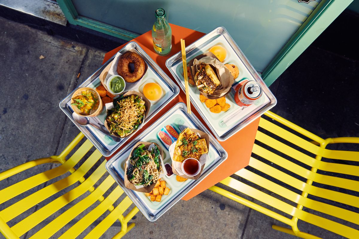 In an overhead photo, a spread of dishes including a mushroom sloppy joe, longevity noodles, and rice rolls sit on lunch trays on an orange outdoor table