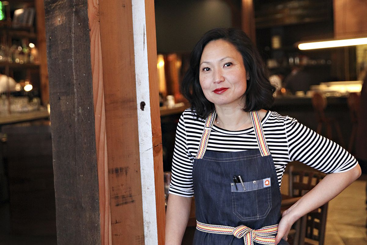 Ann Kim wearing a black and white striped shirt and blue apron leans on a chair, one hand on her hip inside the dining room at Young Joni