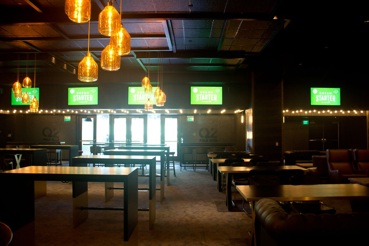The inside of a dark lounge with tables and sofa seating and hanging orange lights and several television screens