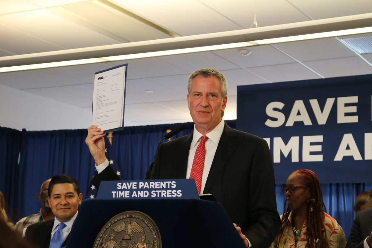 Mayor Bill de Blasio holds up a new application form while announcing changes to middle and high school admissions.
